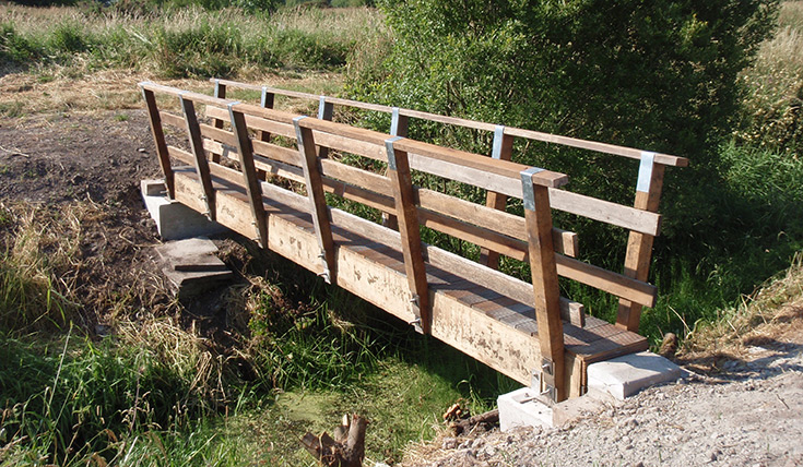 A new wooden footbridge over a ditch